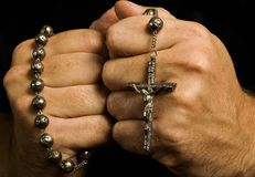 Man shows his deep Christian faith. Individual with strong religious convictions tightly clutches his rosary while praying to God Stock Photography