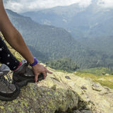 A man shows his hand to unstick from the sole of hiking boots Stock Photos