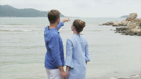 A man shows his hand towards the horizon and large stones on the sea. Young couple holding hands on the ocean shore.  stock video