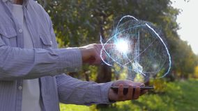 Man shows hologram with sailing ship. Unrecognizable man shows conceptual hologram with sailing ship. Farmer on the background of the apple orchard in casual stock video