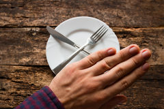 Man shows refusal to eat. On wooden table Royalty Free Stock Photos