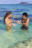 Man shows seashells to a young woman Royalty Free Stock Photography