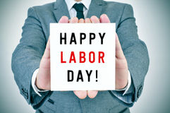 Man shows a signboard with the text happy labor day. Closeup of a young man in suit showing a signboard with the text happy labor day written in it stock photo
