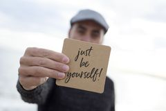 Man shows signboard with the text just be yourself. Closeup of a young caucasian man wearing a flat cap outdoors shows a signboard with the text just be yourself stock images