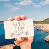 Man shows a signboard with the text never stop dreaming Stock Images