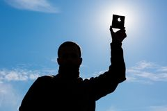 Man shows sun eclipse. Partial Sun eclipse. Man covering a strong sunlight by dark plate and shows sun eclipse. man hand silhouette on blue sky Royalty Free Stock Photo