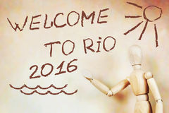Man shows text Welcome to Rio 2016. Abstract conceptual image with a wooden puppet Royalty Free Stock Images