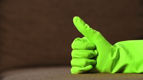 Man shows thumb up in green latex glove stock footage