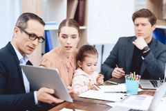A man shows a woman with a child something on the tablet. A men shows a women with a child something on the tablet. They are in the business office. A women has Stock Photo