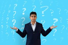 Man shrugging in front of a blue background with question marks pattern stock photography