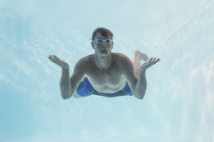 Man shrugging shoulders underwater in swimming pool Stock Photos