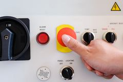 Man is shutting off a machine with the emergency button.  royalty free stock photography