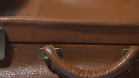 Man shutting vintage leather suitcase, packing for vacation, preparing for trip. Stock footage stock video footage