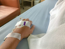 Man is sick and has  a IV tube on his hand Royalty Free Stock Images