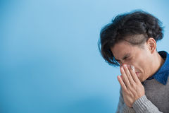 Man is sick and sneezing. With blue background, asian Royalty Free Stock Photo