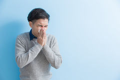 Man is sick and sneezing. With blue background, asian Stock Images