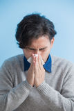 Man is sick and sneezing. With blue background, asian Stock Photography