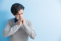Man is sick and sneezing. Man  sick and sneezing with blue background, asian Royalty Free Stock Images