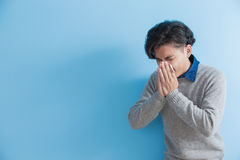 Man is sick and sneezing. With blue background, asian Stock Image