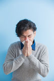 Man is sick and sneezing. With blue background, asian Royalty Free Stock Photography