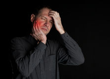 Man with a sick tooth keeps cheek hand. On a black background Royalty Free Stock Image