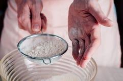 Man sifting flour for pizza dough Stock Photos
