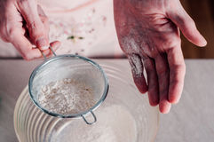 Man sifting flour for pizza dough Stock Photo