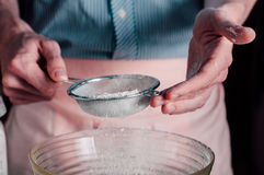 Man sifting flour for pizza dough Stock Images