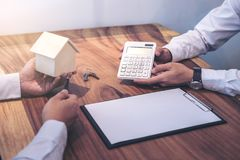 Man sign a home insurance policy on home loans, Agent agent hold. S loan investment chart graph documents and calculating table installment payment, Real Estate royalty free stock photos