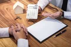 Man sign a home insurance policy on home loans, Agent agent hold. S loan investment chart graph documents and calculating table installment payment, Real Estate stock photo