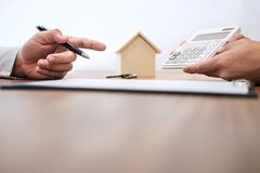 Man sign a home insurance policy on home loans, Agent agent hold. S loan investment chart graph documents and calculating table installment payment, Real Estate royalty free stock photo