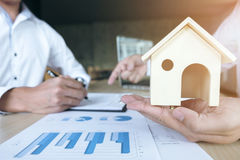 Man sign a home insurance policy on home loans, Agent holds home stock photos