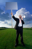 Man with sign and megaphone. A man standing in a green field, holding a blank sign and shouting through a megaphone Royalty Free Stock Photos