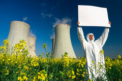 Man with sign at nuclear plant. A view of a man in a protective suit, holding a blank sign in front of a nuclear power plant stock image