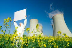 Man with sign at nuclear plant. A view of a man in a protective suit, holding a blank sign in front of a nuclear power plant stock photo