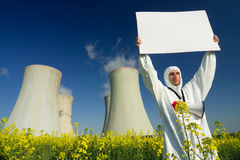 Man with sign at nuclear plant. A view of a man in a protective suit, holding a blank sign in front of a nuclear power plant royalty free stock photography