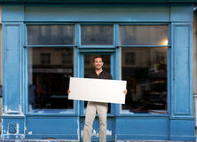 Man with sign by shop Stock Image