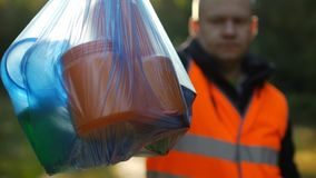A man in a signal orange vest holds a package with garbage on the background of nature, forest, close-up, garbage collection stock photo