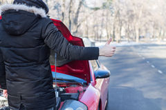 Man signaling problems with the car on winter road. Man signaling problems with broken car on winter road Stock Photos
