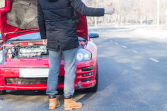 Man signaling problems with the car on winter road. Man signaling problems with broken sport car on winter road Royalty Free Stock Images