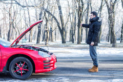 Man signaling problems with the car on winter road. Man signaling problems with broken sport car on winter road Stock Photography