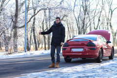 Man signaling problems with sport car on winter road. Stock Photos