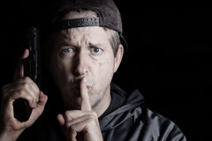 Man signaling to be quite while holding weapon Stock Photos