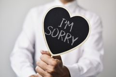 Man with a signboard with the text I am sorry Stock Photos