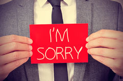 Man with signboard with the text I am sorry Stock Image