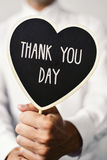 Man with signboard with the text thank you day. A young caucasian man wearing a white shirt shows a heart-shaped signboard with the text thank you day written in Royalty Free Stock Image