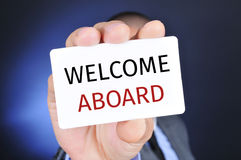 Man with a signboard with the text welcome aboard Royalty Free Stock Images