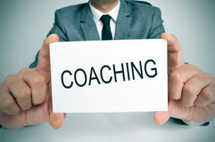 Man with a signboard with the word coaching Stock Photography