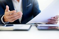 Man signing a car insurance policy, the agent is holding the doc. Ument Royalty Free Stock Photography