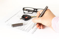 Man signing a car purchase form Royalty Free Stock Images